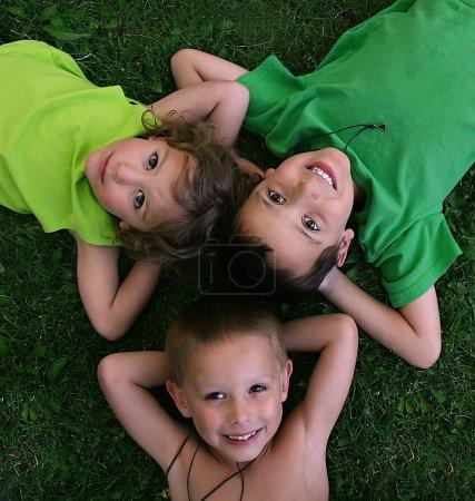 Photo pour Trois enfants allongés dans l'herbe - image libre de droit
