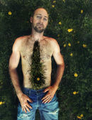 Shirtless man surrounded by weeds