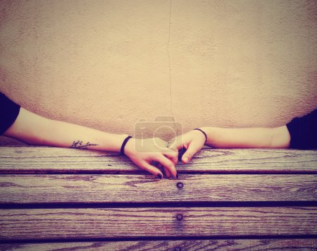 Photo for Two people holding hands on a bench done with a retro vintage instagram filter - Royalty Free Image