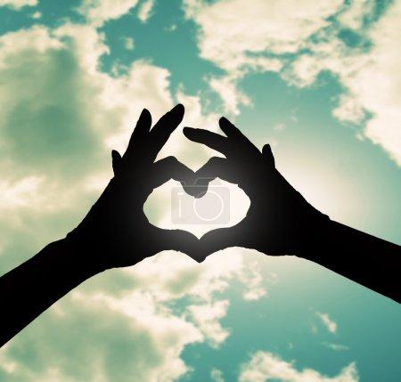 Dos manos haciendo forma de corazón en el cielo