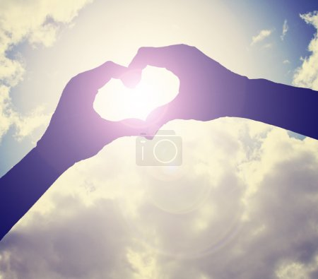 Two hands making heart shape in sky