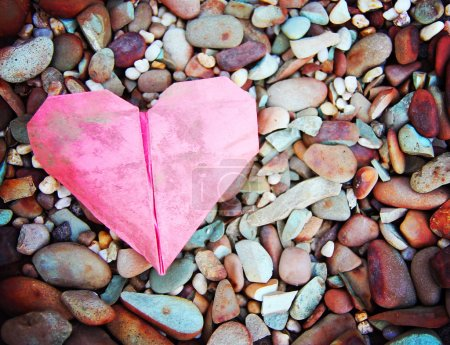 discarded paper heart on a rocks