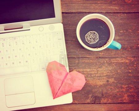 Photo pour Ordinateur portable ou ordinateur portable avec tasse de café et coeur d'origami sur une vieille table en bois tonique avec un filtre instagram vintage rétro - image libre de droit