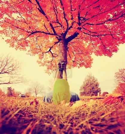 Photo pour Pieds reposant sur un tronc d'arbre pendant l'automne lorsque les feuilles tournent couleurs tonifiées avec un filtre instagram vintage rétro - image libre de droit