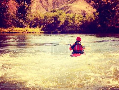 Woman kayaking on rough river