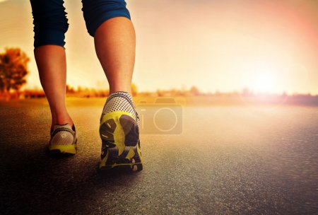 Photo for A woman with an athletic pair of legs going for a jog or run during sunrise or sunset - healthy lifestyle concept done with an instagram like filter - Royalty Free Image