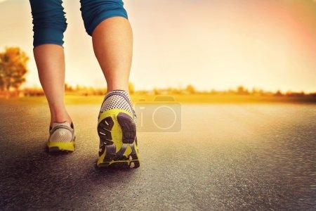 Photo pour Une femme avec une paire de jambes athlétiques allant faire du jogging ou courir pendant le lever ou le coucher du soleil concept de mode de vie sain fait avec un instagram comme filtre - image libre de droit