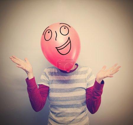 Photo pour Une personne avec un ballon devant son visage vintage tonique pour un look rétro - image libre de droit