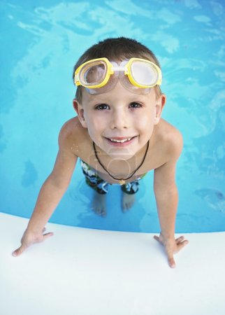 Photo for A young boy with swimming glasses in pool - Royalty Free Image