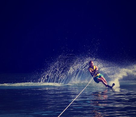 Photo for A young woman water skiing on a lake done with a retro vintage instagram filter - Royalty Free Image
