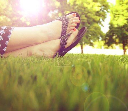 Photo pour Jolis pieds sur l'herbe au coucher du soleil avec les ongles peints et sandales sur - image libre de droit