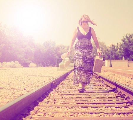 Photo pour Une fille descendant les voies ferrées avec une valise et un chapeau fait avec un filtre vintage rétro comme instagram - image libre de droit