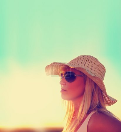 Photo pour Une jolie femme montrant son profil au lever ou au coucher du soleil tonique avec traitement croisé instagram comme filtre vintage rétro - image libre de droit