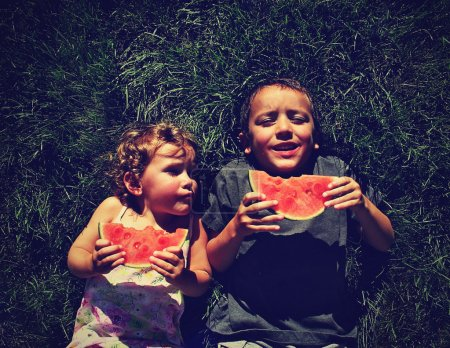 Two kids eating watermelon