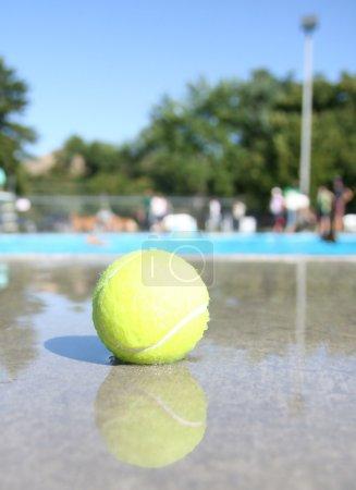 Photo pour Une balle de tennis dans une piscine publique locale - image libre de droit