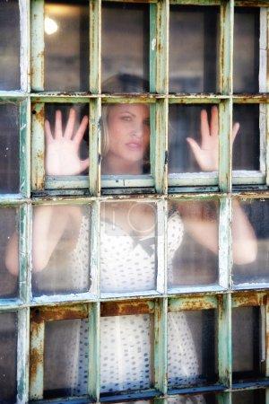 Photo pour Une jolie fille dans une fenêtre d'une vieille prison - image libre de droit