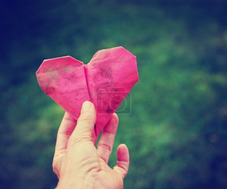 Hand holding an origami heart