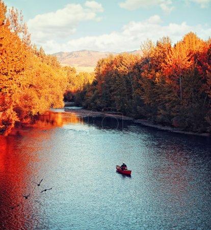 Photo pour Une rivière qui coule en automne avec un kayakiste pagayant dans l'eau - image libre de droit