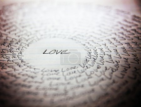 Photo for The word love written on a lined piece of school paper in ink with a vignette and a circle of love (very shallow depth of field - focus on the bottom of the word love) - Royalty Free Image