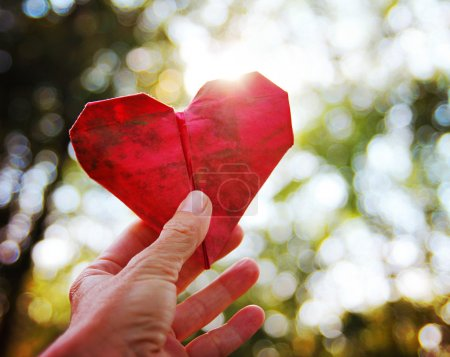 Hand holding origami paper heart