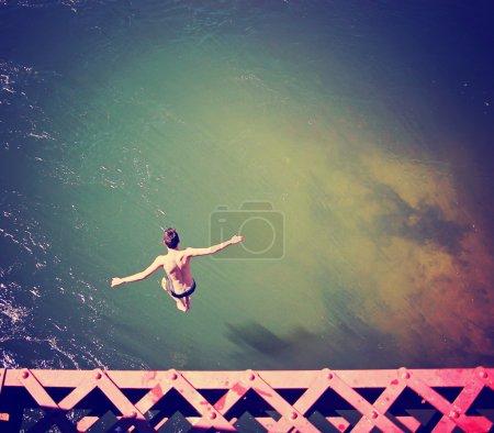 Boy jumping of train bridge