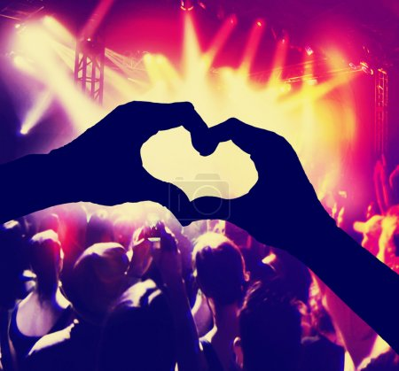 Photo pour A crowd of people at a concert with heart shaped hands over the stage toned with a retro vintage instagram filter - image libre de droit