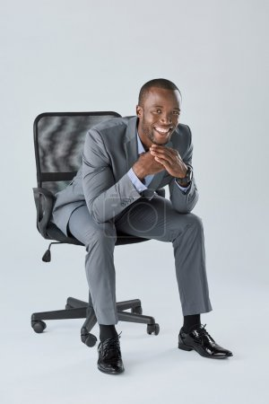 Happy smiling business man sitting in chair