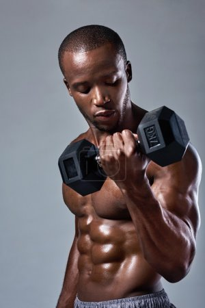 Photo for Muscular black african man with well defined muscles abs adominal lifting weights - Royalty Free Image