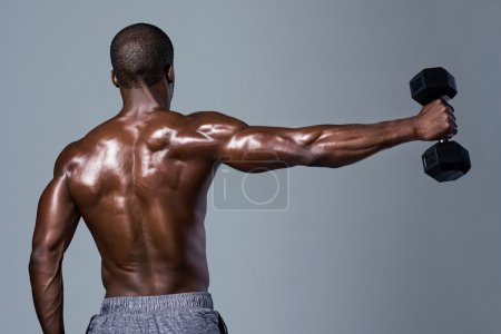 Muscular back defined anonymous black man lifting weights isolated in studio