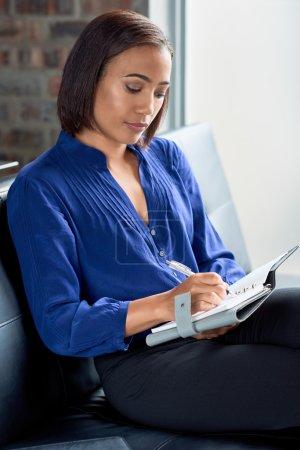 female entrepreneur taking notes being organised