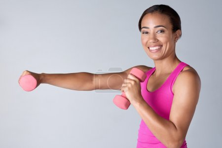 Happy woman exercising with dumbbells in studio