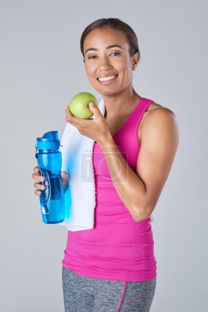 Fit woman holding water bottle and apple