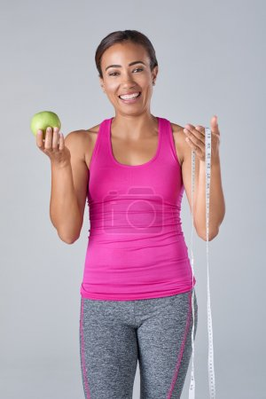 Fit woman holding measuring tape and apple