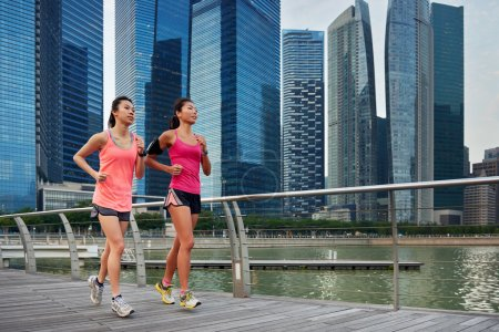 Photo for Asian chinese sporty running women working out jogging outdoors along urban city harbor sidewalk morning - Royalty Free Image