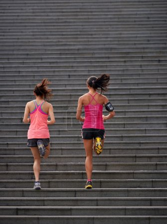 Photo for Active sporty women working out running up stairs outdoors for morning workout - Royalty Free Image
