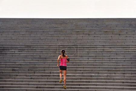 Photo pour Femme sportive travaillant en cours d'exécution dans les escaliers à l'extérieur pour l'entraînement du matin - image libre de droit