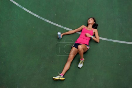 Exhausted sporty woman runner laying on basketball...