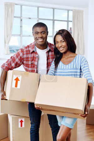 Photo for Young black african couple moving boxes into new home together making a successful life - Royalty Free Image