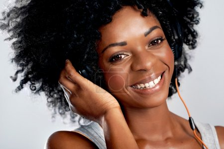 Photo for Closeup portrait of a smiling african woman with afro and headphones against isolated background - Royalty Free Image