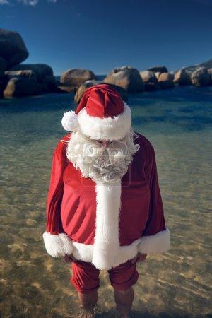 Man in a Santa Claus costume on beach