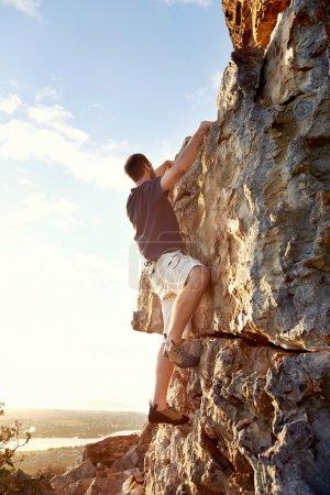 Rock climber climbing up steep of mountain