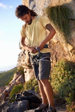 Man putting on harness to go rock climbing