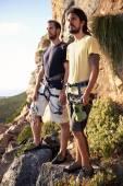 Two men holding rock climbing equipment