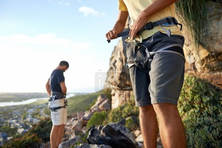Two men putting on climbing equipment