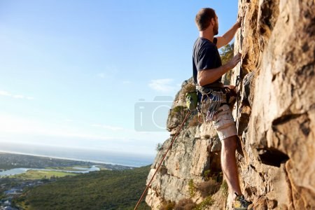 male rockclimber climbing up mountain