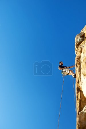 Photo for A man high up the cliff of amountain climbing going down by rope -Rockclimbing - Royalty Free Image