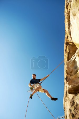 rockclimber going down steep mountain