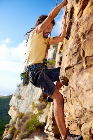 Photo for A dreadlocked rockclimbing guy finding a foothold on a steep mountain - Royalty Free Image