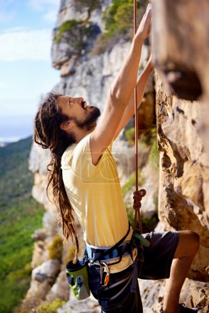 Photo for A man with dreadlocks climbing up a steep mountain with a harness and rope and looking up - Royalty Free Image