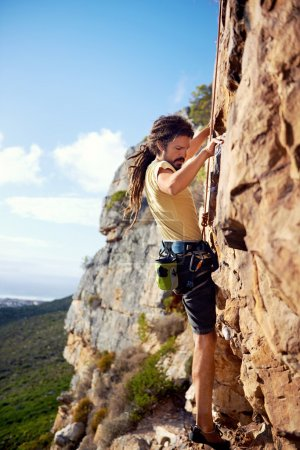 Photo for A rockclimbing guy with dreadlocks finding a foothold on a steep mountain - Royalty Free Image